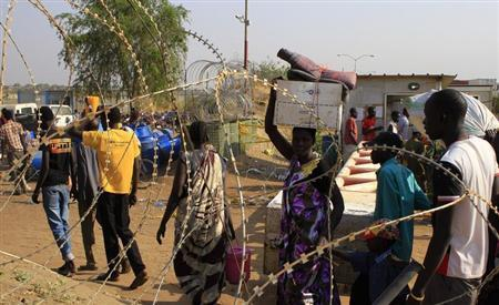 Displaced people walk past razor wire at Tomping camp, where some 15,000 displaced people who fled their homes are sheltered by the United Nations, near Juba