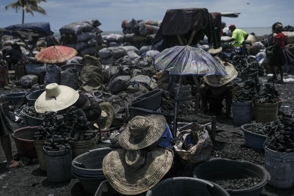 Vendors wear hats for shade as they sell cooking coal at a market in Cap-Haitien, Haiti, Thursday, July 22, 2021. The city of Cap-Haitien will hold events to honor slain President Jovenel Moïse on Thursday ahead of Friday's funeral. (AP Photo/Matias Delacroix)