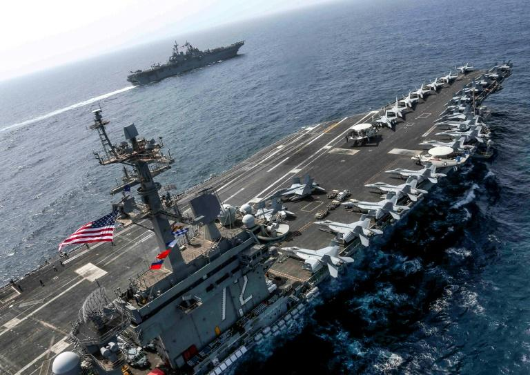 This handout picture released by the US Navy on May 17, 2019 shows the Nimitz-class aircraft carrier USS Abraham Lincoln in the foreground as it sails in the Arabian Sea