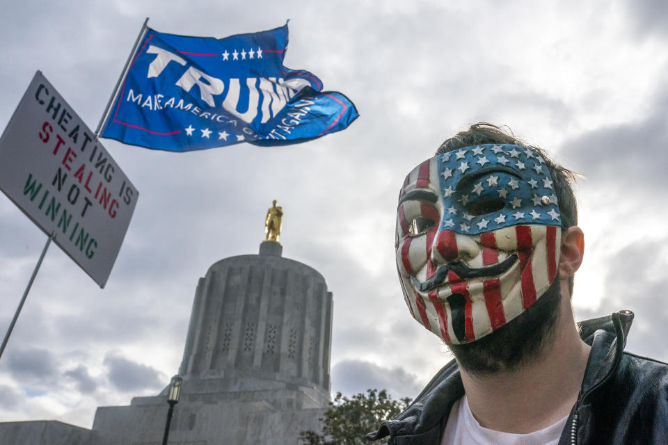 SALEM, OR - NOVEMBER 07: A protester in a Guy Fawkes mask stands in front of the Oregon State Capitol building during a Stop the Steal rally on November 7, 2020 in Salem, Oregon. Angry supporters of President Trump took to the streets across the country following reporting that President-elect Joe Biden had won the election. (Photo by Nathan Howard/Getty Images)