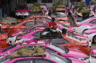 """Workers from local taxi cooperatives assemble miniature gardens on the rooftops of unused taxis parked in Bangkok, Thailand, Thursday, Sept. 16, 2021. Taxi fleets in Thailand are giving new meaning to the term """"rooftop garden,"""" as they utilize the roofs of cabs idled by the coronavirus crisis to serve as small vegetable plots and raise awareness about the plight of out of work drivers. (AP Photo/Sakchai Lalit)"""
