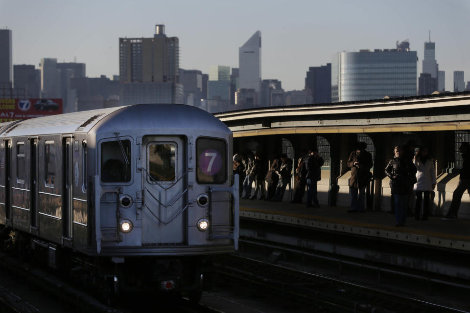 Commuters wait on the platform as a train passes through the 40th St-Lowry St Station, where a man was killed after being pushed onto the subway tracks, in the Queens section of New York, Friday, Dec. 28, 2012. Police are searching for a woman suspected of pushing the man and released surveillance video Friday of her running away from the station. (AP Photo/Seth Wenig)