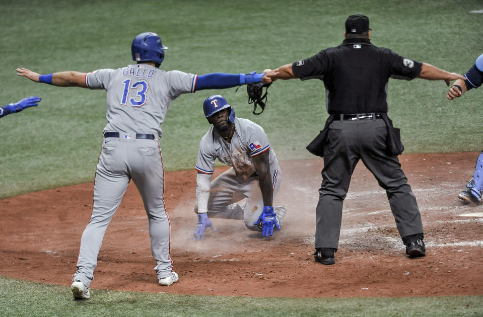 """Texas Rangers' Adolis Garcia, center, looks up to see Joey Gallo (13) and home plate umpire Sam Holbrook, right, signal """"safe"""" after a play at the plate during the seventh inning of a baseball game against the Tampa Bay Rays on Wednesday, April 14, 2021, in St. Petersburg, Fla. Garcia was ruled out after replay. (AP Photo/Steve Nesius)"""