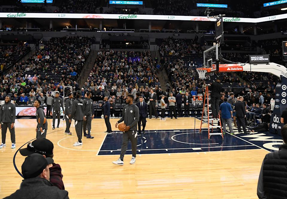 The Minnesota Timberwolves look on as workers inspect a hoop before the game against the Milwaukee Bucks.