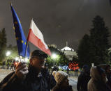 FILE - In this Jan. 23, 2020, file photo, a man holding a Poland and European Union flags take part in a protest outside Poland's parliament building in Warsaw, Poland. The European Union still hasn't completely sorted out its messy post-divorce relationship with Britain — but it has already been plunged into another major crisis. This time the 27-member union is being tested as Poland and Hungary block passage of its budget for the next seven years and an ambitious package aimed at rescuing economies ravaged by the coronavirus pandemic. (AP Photo/Czarek Sokolowski, File)