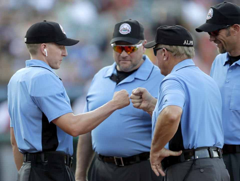 FILE - In this July 10, 2019, file photo, home plate umpire Brian deBrauwere, left, huddles with officials while wearing an earpiece connected to a ball and strikes calling system before the Atlantic League All-Star minor league baseball game in York, Pa. DeBrauwere wore the earpiece connected to an iPhone in his ball bag which relayed ball and strike calls upon receiving it from a TrackMan computer system that uses Doppler radar. The independent Atlantic League became the first American professional baseball league to let the computer call balls and strikes during the all star game. Umpires agreed to cooperate with Major League Baseball in the development and testing of an automated ball-strike system as part of a five-year labor contract announced Saturday, Dec. 21, two people familiar with the deal told The Associated Press. The Major League Baseball Umpires Association also agreed to cooperate and assist if Commissioner Rob Manfred decides to utilize the system at the major league