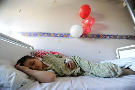 A boy sleeps while receiving treatment inside The Children's Hospital in Damascus