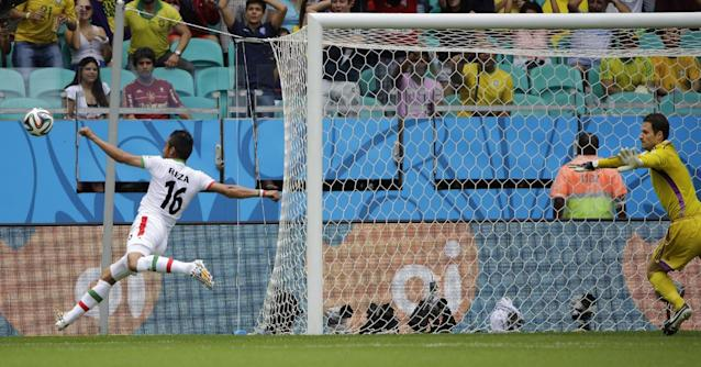 Iran's Reza Ghoochannejhad, left, tries to follow up after the ball rebounded off the bar during the group F World Cup soccer match between Bosnia and Iran at the Arena Fonte Nova in Salvador, Brazil, Wednesday, June 25, 2014. (AP Photo/Sergei Grits)
