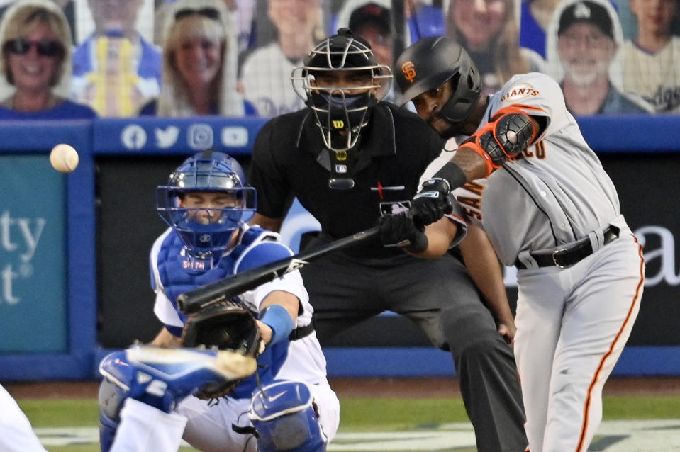 San Francisco Giants' Jaylin Davis, right, hits a solo home run while Los Angeles Dodgers catcher Will Smith watches along with home plate umpire Edwin Moscoso during the third inning of a baseball game Friday, July 24, 2020, in Los Angeles. (AP Photo/Mark J. Terrill)