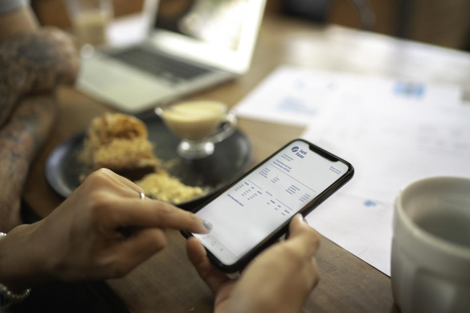 Woman checking account statement of her digital investment on her mobile phone