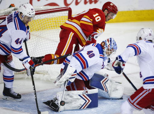 New York Rangers goalie Alexandar Georgiev, right, manages to deflect the puck away as Calgary Flames' Derek Ryan crashes the net behind him during the third period of an NHL hockey game in Calgary, Alberta, Friday, March 15, 2019. (Jeff McIntosh/The Canadian Press via AP)