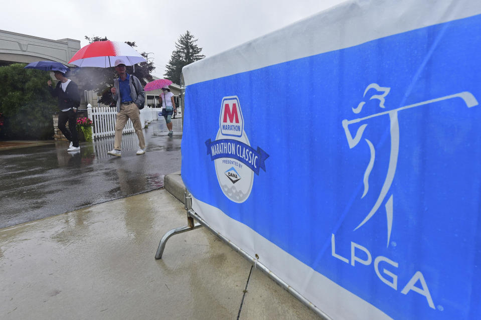 Fans walk near the clubhouse as play is suspended during the final round of the Marathon LPGA Classic golf tournament at Highland Meadows Golf Club in Sylvania, Ohio, Sunday, July 11, 2021, in Sylvania, Ohio. (AP Photo/David Dermer)