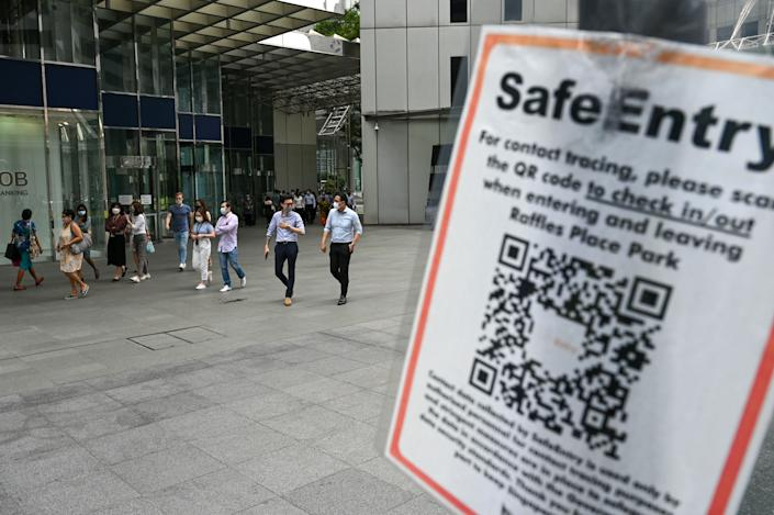 A Covid-19 coronavirus contact tracing sign is pictured as people walk out during lunch break at the Raffles Place financial business district in Singapore on September 14, 2021. (Photo by Roslan RAHMAN / AFP) (Photo by ROSLAN RAHMAN/AFP via Getty Images)