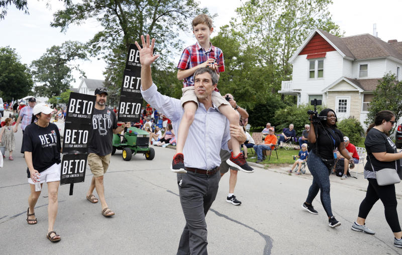 Democratic presidential candidate former Texas Congressman Beto O'Rourke carries his son Henry on his shoulders as he walks in the Independence Fourth of July parade, Thursday, July 4, 2019, in Independence, Iowa. (AP Photo/Charlie Neibergall)