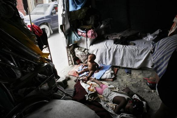 Children rest in a tent along the streets of Route des Rails in Port-au-Prince, July 21, 2010.