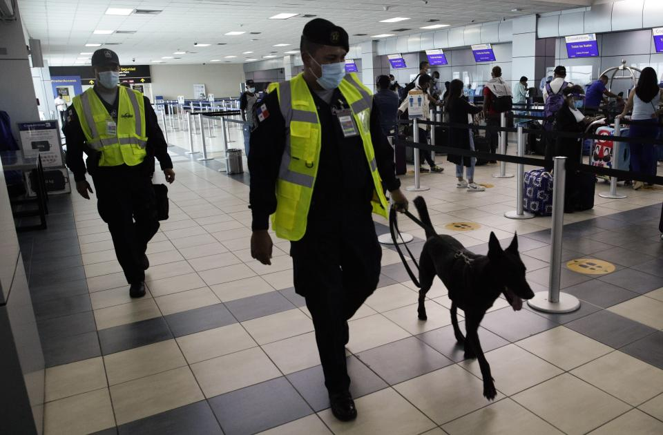 A police officer walks with his search dog as passengers check-in at Tocumen International Airport in Panama City, Monday, Oct. 12, 2020. Panama is lifting a broad spectrum of COVID-19 pandemic-related restrictions on Monday, including re-opening international flights and allowing hotels, casinos, and tourism-related activities. (AP Photo/Arnulfo Franco)