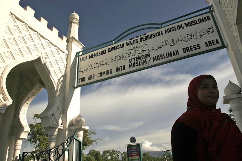 FILE - In this Sept. 13, 2009 file photo, a Muslim woman walks past beneath a sign advising people to wear Muslim attire at Baiturrahman Grand Mosque in Banda Aceh, Aceh province, Indonesia. An Indonesian woman who was gang-raped by men who accused her of having extramarital sex may be caned publicly for violating Islamic law, an official said Wednesday, May 7, 2014. The 25-year-old widow said she was raped by eight men who allegedly found her having sex with a married man in her house. The men reportedly beat the man, doused the two with sewage, and then turned them over to Islamic police in conservative Aceh province. Indonesia, the world's most populous Muslim nation of 240 million people, has a policy of secularism but allows Aceh, a predominantly Muslim province on the northern tip of Sumatra, to implement a version of Sharia Islamic law. (AP Photo/Heri Juanda, File)