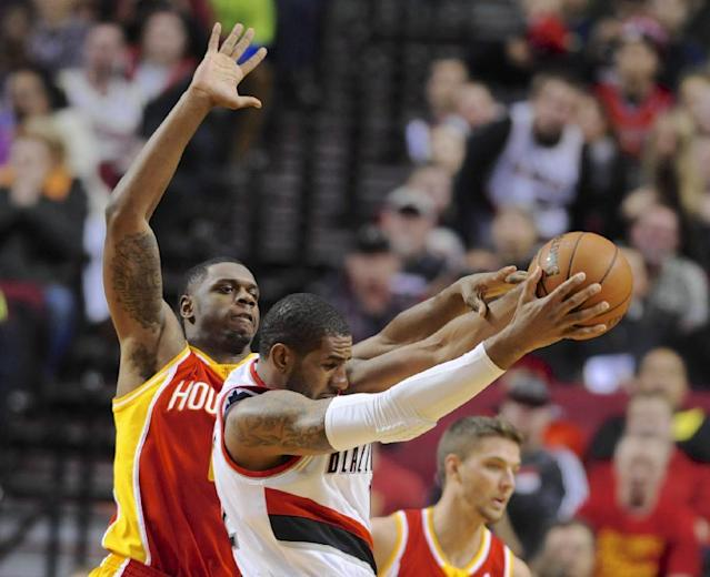 Houston Rockets' Terrence Jones, left, defends against Portland Trail Blazers' LaMarcus Aldridge, center, during the first half of an NBA basketball game in Portland, Ore., Thursday Dec. 12, 2013. (AP Photo/Greg Wahl-Stephens)