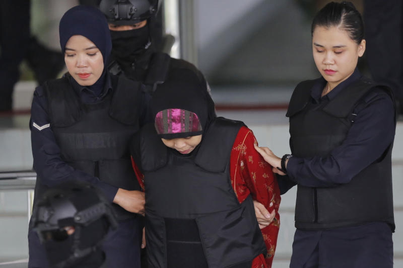 Indonesian Siti Aisyah, center, is escorted by police as she leaves her court hearing at the Shah Alam High Court in Shah Alam, Malaysia, Thursday, Aug. 16, 2018. The Malaysian court has ordered the two women, Siti Aisyah and Vietnamese Doan Thi Huong to enter their defense over the murder of North Korean leader's half-brother in a brazen assassination that has gripped the world. (AP Photo/Yam G-Jun)