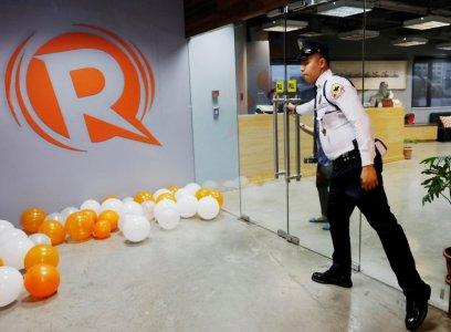 FILE PHOTO: A guard opens a door at the office of Rappler in Pasig, Metro Manila, Philippines January 15, 2018. REUTERS/Dondi Tawatao/File Photo