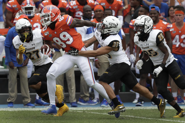 Florida wide receiver Tyrie Cleveland (89) tires to escape Towson safety S.J. Brown II, left, defensive backs Coby Tippett (35) and Terrill Gillette-Rodgers (25) after a pass reception during the first half of an NCAA college football game, Saturday, Sept. 28, 2019, in Gainesville, Fla. (AP Photo/John Raoux)