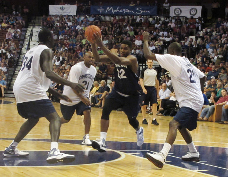 **CORRECTS TO SOULEYMANE WANE (34) AND RICKY MOORE (21)** Memphis Grizzlies forward Rudy Gay drives by former Connecticut basketball players Souleymane Wane (34) and Ricky Moore (21) during the Jim Calhoun Celebrity Classic, Saturday, Aug. 4, 2012, in Uncasville, Conn. (AP Photo/Pat Eaton-Robb)