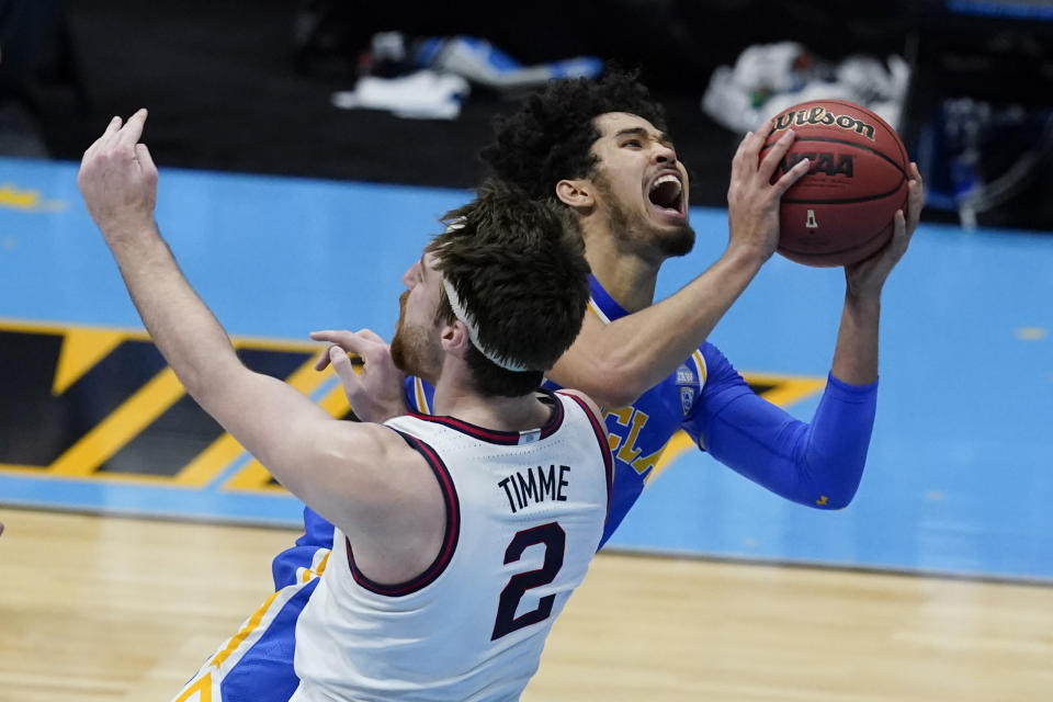 UCLA guard Johnny Juzang, rear, drives to the basket over Gonzaga forward Drew Timme (2) during the second half of a men's Final Four NCAA college basketball tournament semifinal game, Saturday, April 3, 2021, at Lucas Oil Stadium in Indianapolis. Juzang was called for charging. (AP Photo/Darron Cummings)