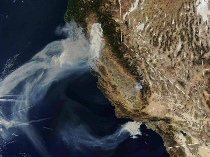 Nasa Earth Observatory satellite image captured on 9 November, 2018, shows the Camp Fire (top) burning in Paradise, California, while the Hill and Woolsey Fires (bottom) burn in nouthern California (Joshua Stevens/NASA Earth Observatory/AFP/Getty Images)