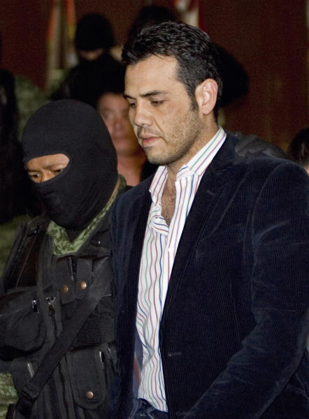 FILE - In this March 19, 2009 file photo, military officers escort alleged drug trafficker Jesus Vicente Zambada Niebla during his presentation to the media in Mexico City. Documents unsealed Thursday, April 10, 2014, by the U.S. Attorney's Office in Chicago show Zambada, a high-ranking member of the Sinaloa cartel in Mexico, pleaded guilty to drug trafficking in April 2013 and has been cooperating with authorities. (AP Photo/Eduardo Verdugo, File)