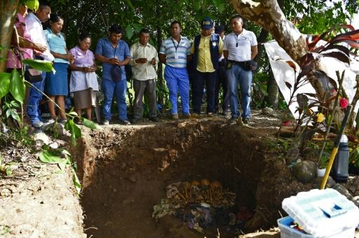 Local residents pray as the human remains -- said to be victims of El Salvador's infamous 1981 Mozote massacre -- were exhumed