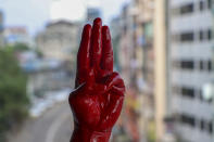 An anti-coup protester shows the three fingered salute of resistance on his red painted hand in memory of protesters who lost their lives during previous demonstrations in Yangon, Myanmar on Tuesday, April 6, 2021. Threats of lethal violence and arrests of protesters have failed to suppress daily demonstrations across Myanmar demanding the military step down and reinstate the democratically elected government. (AP Photo)