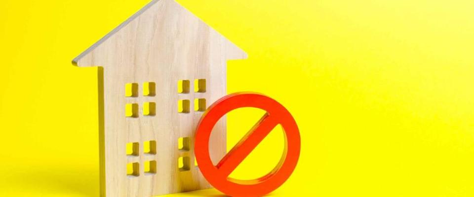 Wooden house figurine and a red symbol NO or ban.