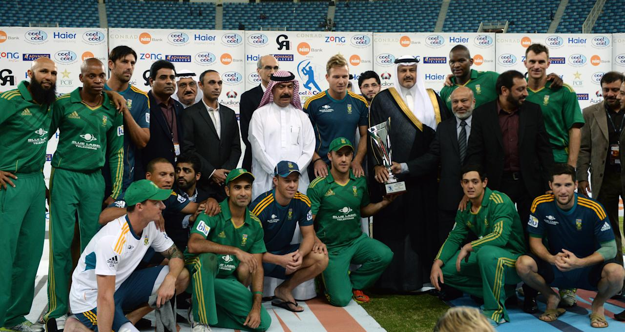 South African cricketers poses with T20 trophy at Dubai stadium after defeating Pakistan on November 15, 2013. South Africa sparked another Pakistan batting collapse to win the second T20 international by six runs, taking the two-match series 2-0. AFP PHOTO/ Asif HASSAN        (Photo credit should read ASIF HASSAN/AFP/Getty Images)