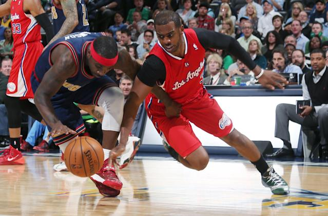 Denver Nuggets guard Ty Lawson, left, pursues a loose ball with Los Angeles Clippers guard Chris Paul in the first quarter of an NBA basketball game in Denver on Monday, March 17, 2014. (AP Photo/David Zalubowski)