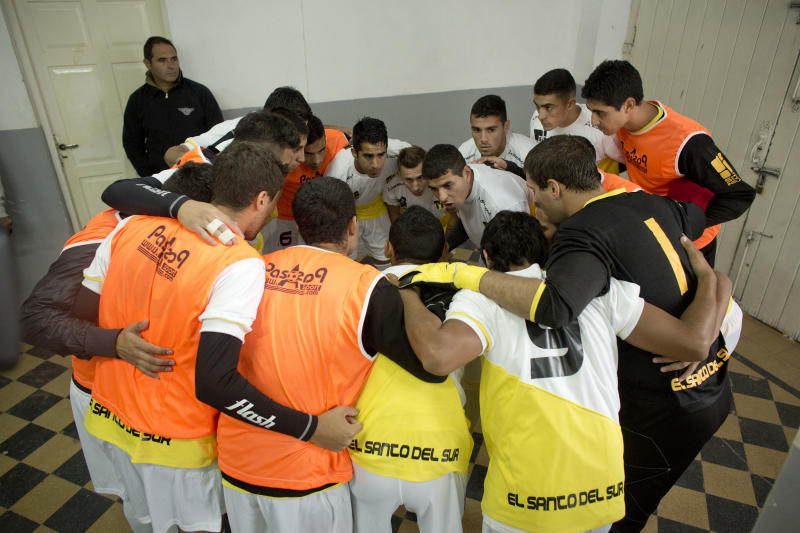 "Soccer players from the team ""Papa Francisco,"" or Pope Francis, huddle before their match against Trefules in Lujan, Argentina, Saturday, April 12, 2014. The new semiprofessional team named after the Argentine pontiff chose the colors of the Vatican flag for their uniforms. (AP Photo/Victor R. Caivano)"