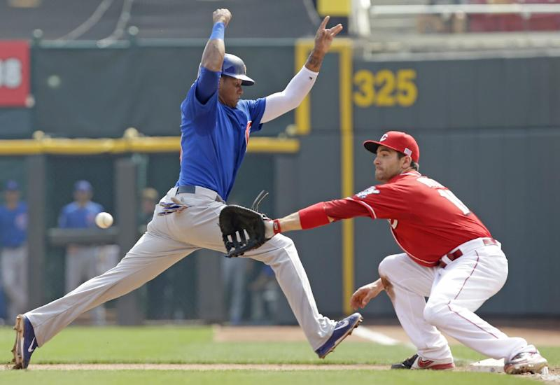 Chicago Cubs' Starlin Castro jumps safely back to first base as Cincinnati Reds first baseman Joey Votto (19) catches a pickoff throw from starting pitcher Mike Leake in the fifth inning of a baseball game, Wednesday, Sept. 11, 2013, in Cincinnati. (AP Photo/Al Behrman)