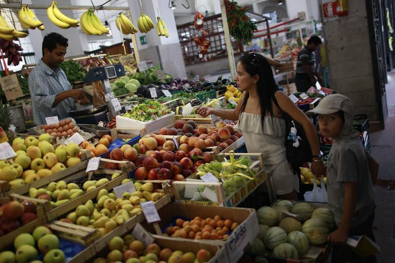 A woman buys fruit in a market in downtown Rome