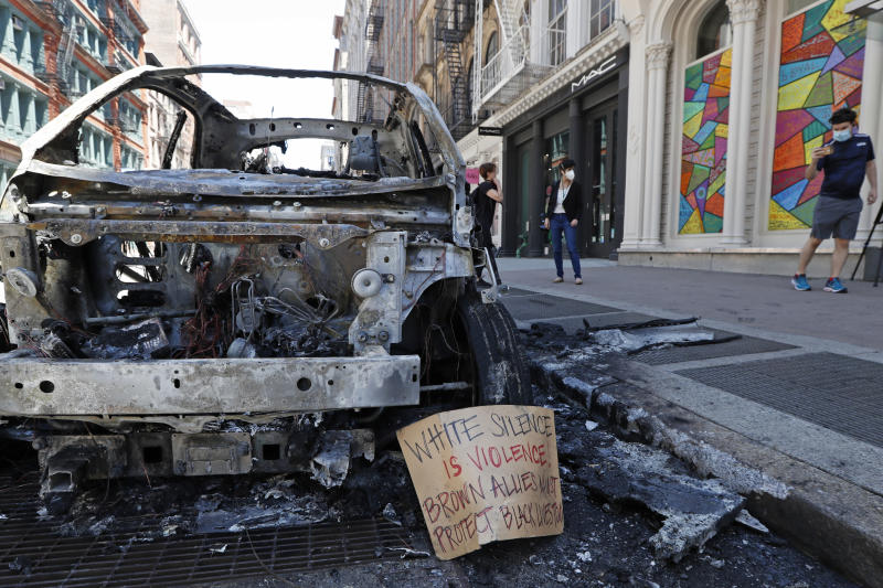 A message is perched against the carcass of a burned out police vehicle, Sunday, May 31, 2020, along a stretch of Broadway in Lower Manhattan in New York. Protesters angry over the death of George Floyd vandalized the area Saturday night. Floyd died in polcie custody in Minneapolis on Memorial Day. (AP Photo/Kathy Willens)