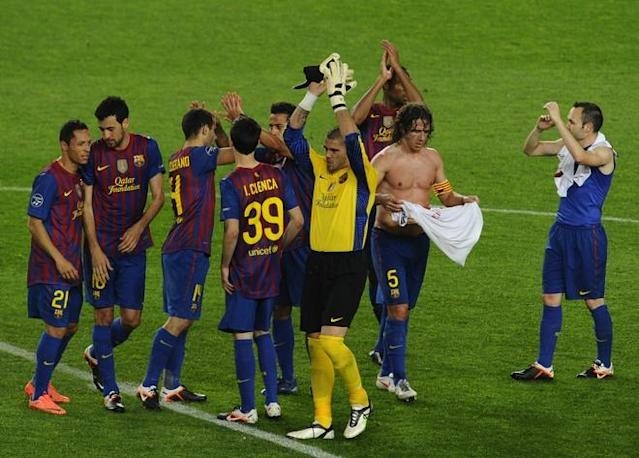 Barcelona's captain Carles Puyol (C) celebrates with team mates at the end of the Champions League quarter-final second leg football match FC Barcelona vs AC Milan on April 3, 2012 at Camp Nou stadium in Barcelona. FC Barcelona defeated AC Milan 3-1 to reach the semi-finals. AFP PHOTO / PIERRE-PHILIPPE MARCOU