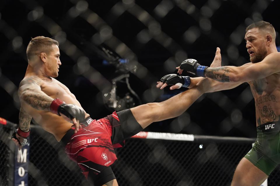 Conor McGregor, right, tries to avoid a kick from Dustin Poirier during a UFC 264 lightweight mixed martial arts bout Saturday, July 10, 2021, in Las Vegas. (AP Photo/John Locher)