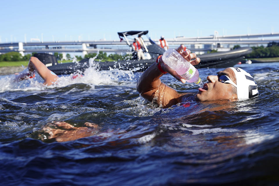 Oussama Mellouli, of Tunisia, grabs a drink while passing through the feeding station during the men's marathon swimming event at the 2020 Summer Olympics, Thursday, Aug. 5, 2021, in Tokyo. (AP Photo/David Goldman)