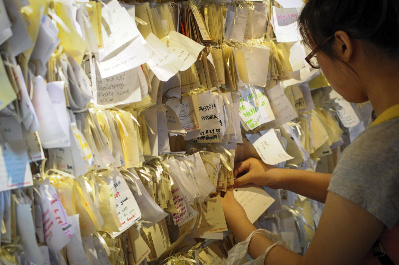 A woman ties a message card for passengers onboard the missing Malaysia Airlines Flight 370 at a shopping mall in Petaling Jaya, near Kuala Lumpur, Malaysia, Thursday, April 10, 2014. With hopes high that search crews are zeroing in on the missing Malaysian jetliner's crash site, ships and planes hunting for the aircraft intensified their efforts Thursday after equipment picked up sounds consistent with a plane's black box in the deep waters of the Indian Ocean. (AP Photo)