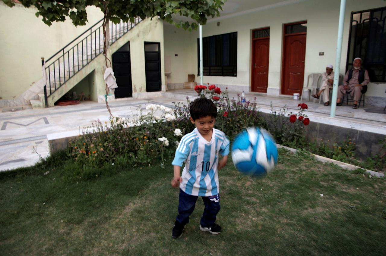 Five year-old Murtaza Ahmedi, an Afghan Lionel Messi fan, wears a shirt signed by Barcelona star Lionel Messi as he plays with a football at his relatives' home in Quetta, Pakistan, May 3, 2016. REUTERS/Naseer Ahmed
