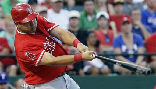 Los Angeles Angels designated hitter Kendrys Morales (8) follows through on a grand slam during the sixth inning of a baseball game against the Texas Rangers, Monday, July 30, 2012, in Arlington, Texas. (AP Photo/LM Otero)