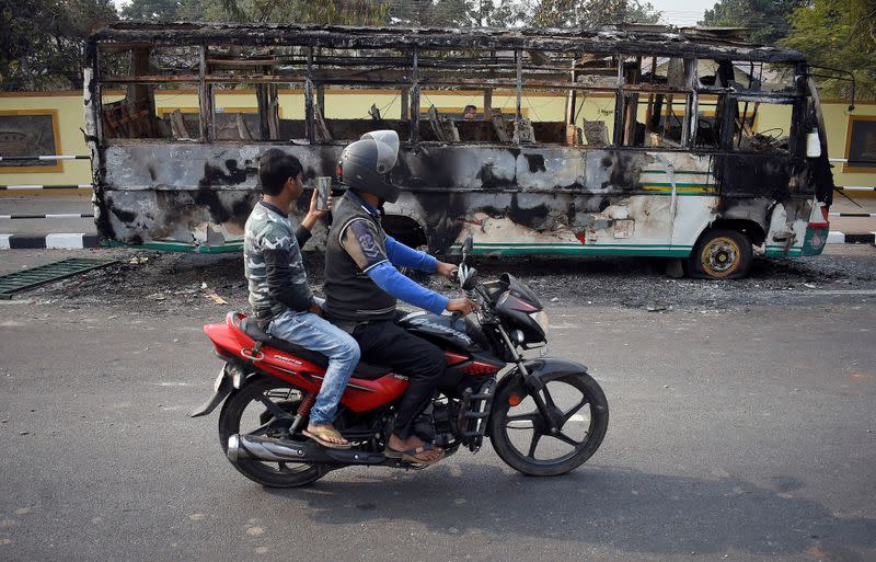 Men ride a motorcycle past a damaged bus that was set on fire by demonstrators, during a protest after India's parliament passed Citizenship Amendment Bill, in Guwahati