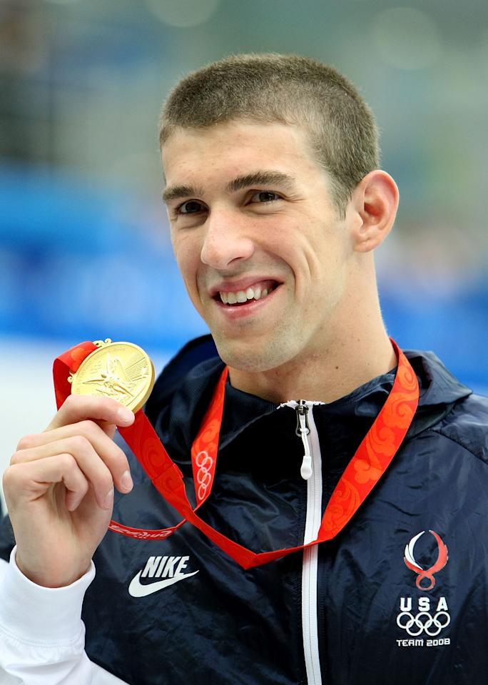 BEIJING - AUGUST 12:  Michael Phelps of the United States poses with the gold medal during the medal ceremony for the Men's 200m Freestyle held at the National Aquatics Center on Day 4 of the Beijing 2008 Olympic Games on August 12, 2008 in Beijing, China.  Michael Phelps of the United States finished the race in first place in a time of 1:42.96 and wins the gold medal and sets a new World Record.  (Photo by Jed Jacobsohn/Getty Images)