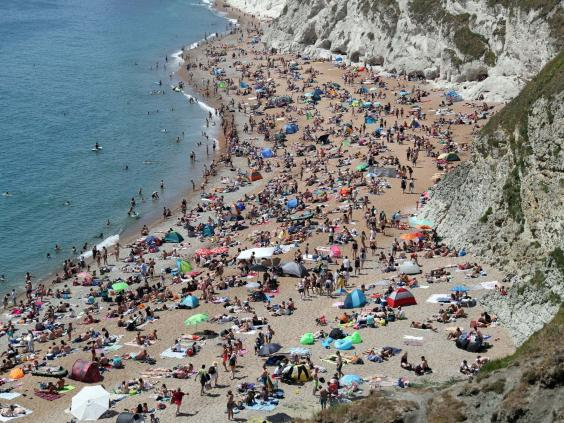 The beach at Durdle Door was crowded on Saturday, while people have been allowed to go outside as long as they keep their distance from others (Andrew Matthews/PA Wire)