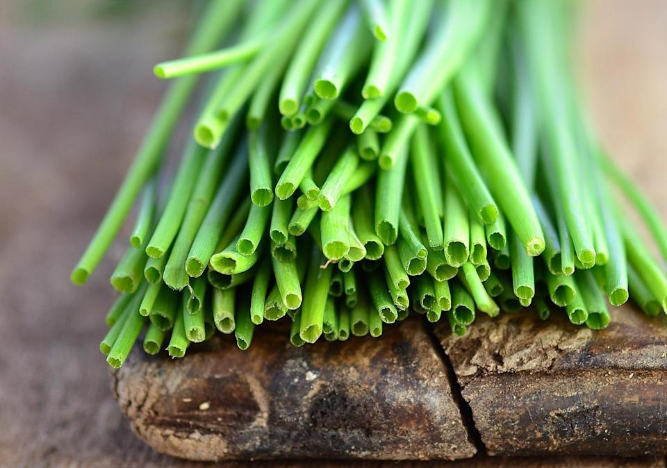 """<p>Left haphazardly in your fridge, chives can easily dry out and leave you garnishing your <a href=""""https://www.thedailymeal.com/recipes-weeknight-dinners-simple?referrer=yahoo&category=beauty_food&include_utm=1&utm_medium=referral&utm_source=yahoo&utm_campaign=feed"""" rel=""""nofollow noopener"""" target=""""_blank"""" data-ylk=""""slk:simple weeknight dinners"""" class=""""link rapid-noclick-resp"""">simple weeknight dinners</a> with withered, tasteless stalks. However, there's a way to store chives that keeps them fresh and hydrated for longer. Simply take a small glass jar and add a few inches of water to the bottom. Place the bottom end of the chives into the water at the bottom of the jar, leaving the tops poking out of the top. Do not wash the chives before placing them in the jar, as the excess moisture can end up speeding up the stems' decay. Cover the chives and the jar with a plastic bag — no need to refrigerate.</p>"""