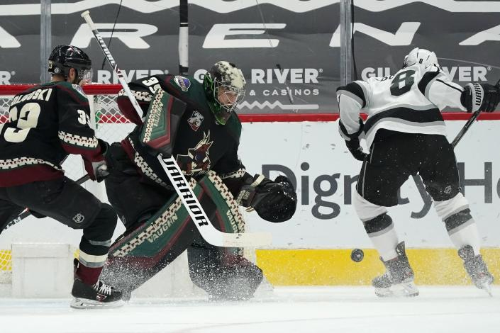 Arizona Coyotes goaltender Darcy Kuemper (35) makes a save on a shot by Los Angeles Kings defenseman Drew Doughty (8) as Coyotes defenseman Alex Goligoski (33) arrives to defend during the first period of an NHL hockey game Monday, May 3, 2021, in Glendale, Ariz. (AP Photo/Ross D. Franklin)
