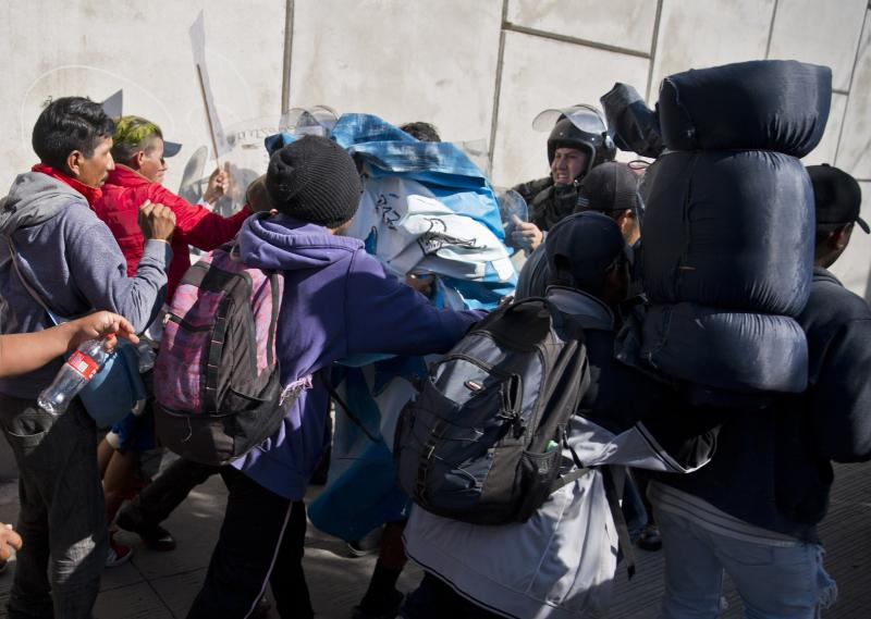 Migrants push past Mexican police at the Chaparral border crossing in Tijuana on Sunday as they try to reach the U.S. Tijuana's mayor has declared a humanitarian crisis in his border city and says that he has asked the United Nations for aid. (ASSOCIATED PRESS)